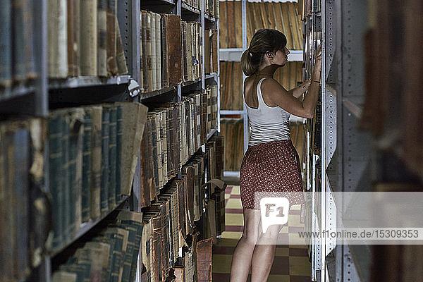 Rückenansicht einer Frau  die in der Nationalbibliothek in Maputo  Mosambik  alte Bücher ausleiht