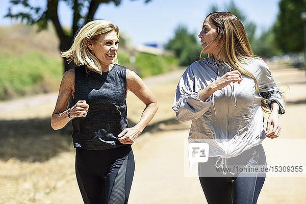 Reife Frau läuft mit ihrer Tochter in einem Park