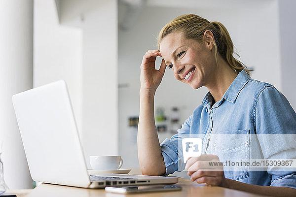 Blonde Frau sitzt im Café und benutzt einen Laptop