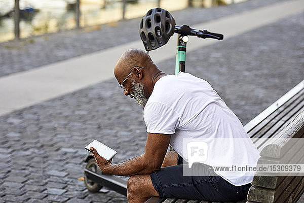 Mature man with E-Scooter sitting on bench in summer using mini tablet  Cologne  Germany