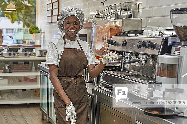 Junge Frau  die in einer Eisdiele arbeitet und eine Kaffeemaschine bedient