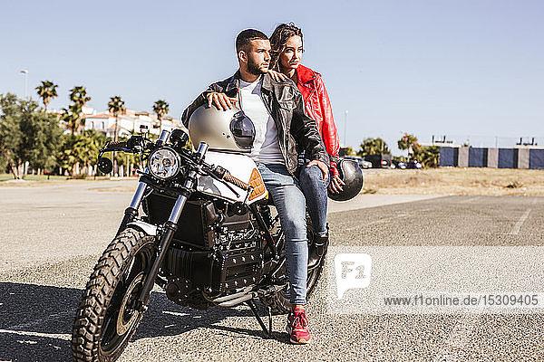 Auf Motorrad sitzendes Paar  das in die Ferne schaut