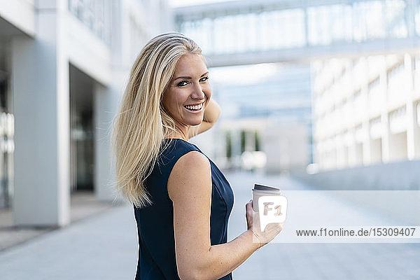 Porträt einer lächelnden blonden Geschäftsfrau mit Kaffee zum Mitnehmen im Sommer