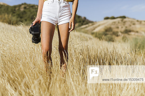 Low section of young woman with camera walking in remote landscape  Granada  Spain