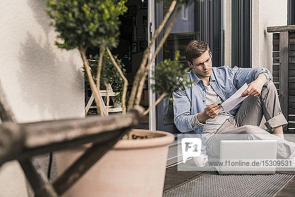 Mann sitzt auf der Terrasse und benutzt einen Laptop