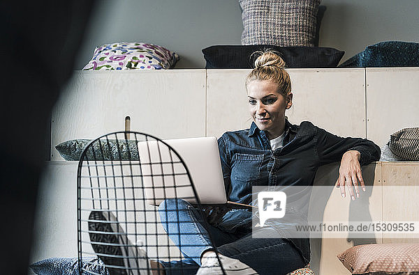 Smiling casual businesswoman using laptop in office lounge