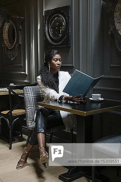 Schicke Frau liest die Speisekarte am Tisch in einem Cafe
