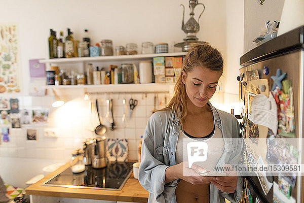 Young woman checking cell phone in kitchen at home