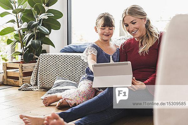 Glückliche Mutter und Tochter nehmen zu Hause Tabletten