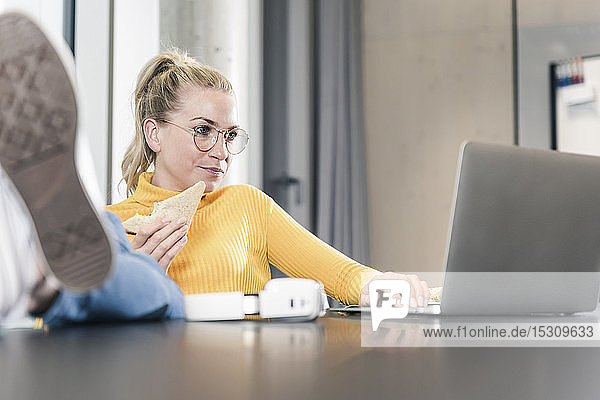 Casual businesswoman sitting at table in office using laptop and eating a sandwich