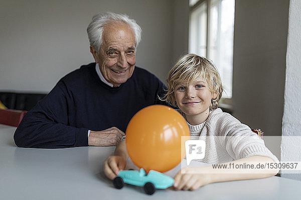 Glücklicher Großvater und Enkel spielen zu Hause mit Spielzeugauto und Ballon