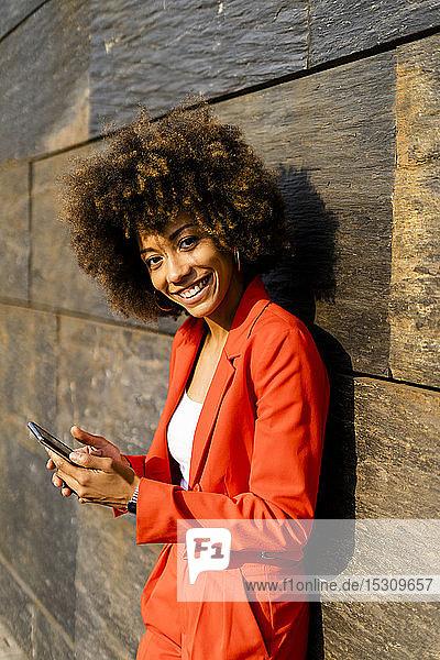 Porträt einer glücklichen jungen Frau mit Smartphone in modischem roten Hosenanzug an der Wand lehnend
