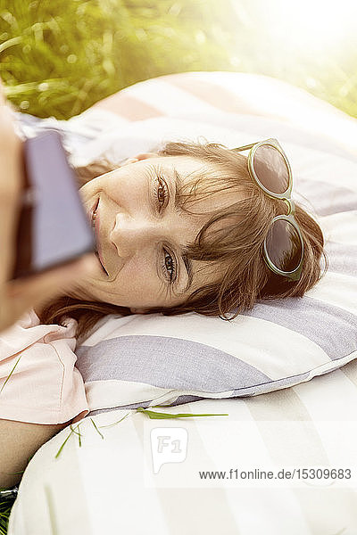 Relaxed woman lying on a meadow using cell phone
