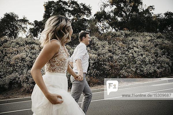 Braut und Bräutigam gehen Hand in Hand auf einer Landstraße