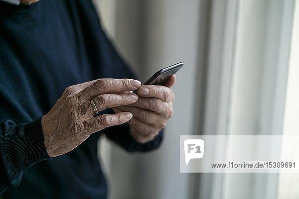 Nahaufnahme eines älteren Mannes bei der Benutzung eines Mobiltelefons zu Hause