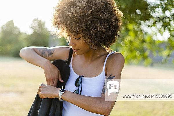 Tätowierte junge Frau mit Umhängetasche im Sommer