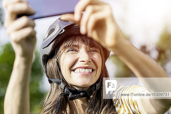 Happy woman wearing bicycle helmet taking a selfie