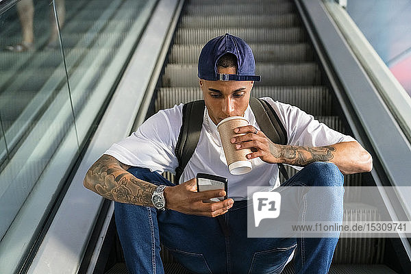 Young man with backpack sitting on escalator looking at cell phone while drinking coffee to go