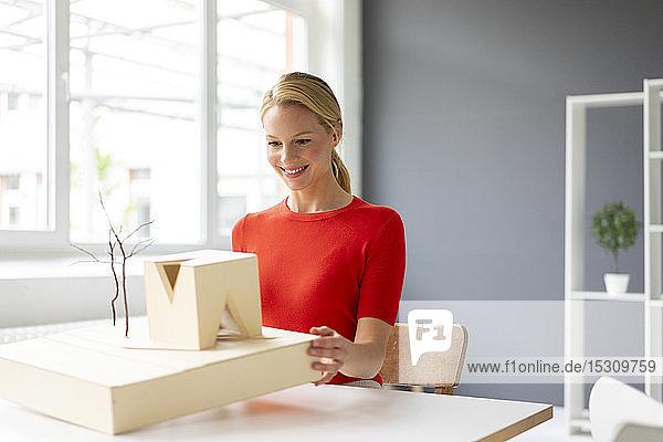 Junge Frau im Büro betrachtet Architekturmodell auf dem Schreibtisch