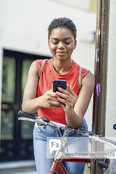 Portrait of smiling young woman leaning on handle bar of bicycle looking at cell phone