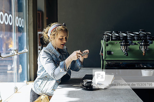 Junge Frau im Café  benutzt Smartphone  fotografiert