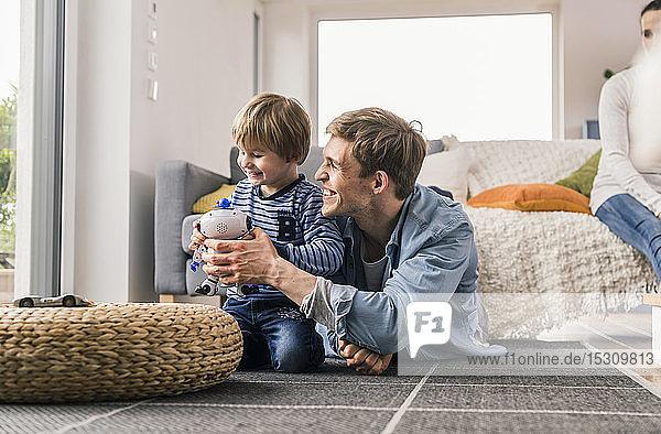 Vater und Sohn liegen auf dem Boden und spielen mit einem Spielzeugroboter