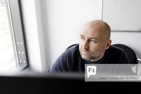Nachdenklicher Mann  der vor einem Computer sitzt und aus dem Fenster schaut