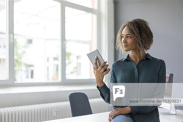Lächelnde Geschäftsfrau mit digitalem Tablet im Büro