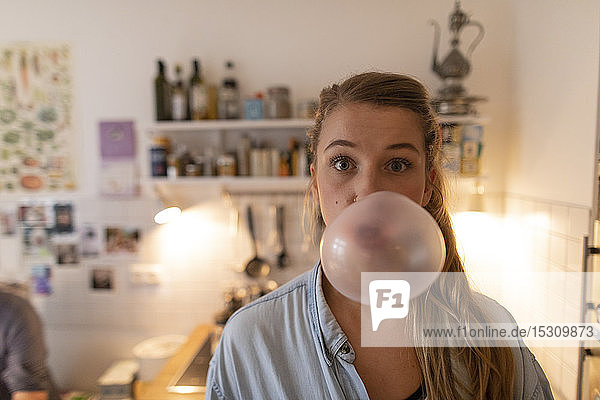 Young woman in kitchen at home making chewing gum bubble