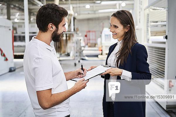 Mitarbeiter unterschreibt Dokument in Fabrik  das von Geschäftsfrau gehalten wird