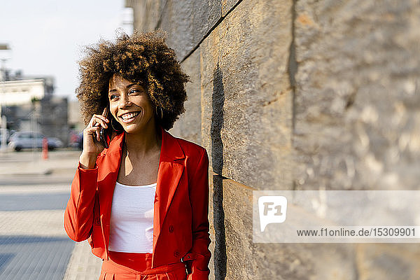 Porträt einer lächelnden jungen Frau am Telefon in einem modischen roten Hosenanzug
