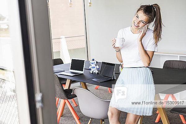 Lächelnde junge Geschäftsfrau im Büro beim Telefonieren
