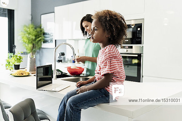 Girl sitting on kitchen counter with laptop and mother in background