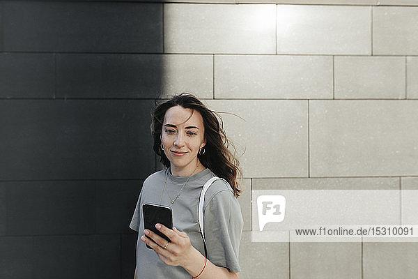 Lächelnde Frau mit Smartphone  graue Wand im Hintergrund