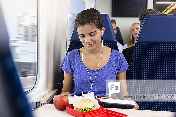 Teenagerin  die allein mit dem Zug reist  Musik hört  einen Imbiss isst