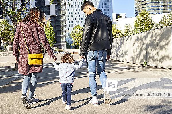 Eltern und kleines Mädchen halten sich an den Händen und gehen zusammen in Barcelona  Spanien
