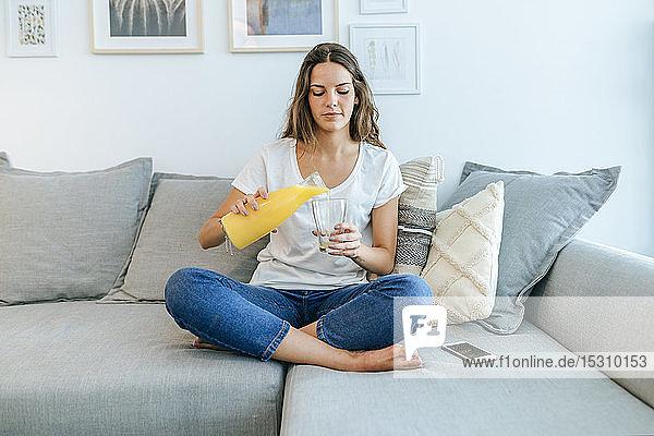 Junge Frau sitzt auf einem Sofa und gießt Orangensaft in ein Glas
