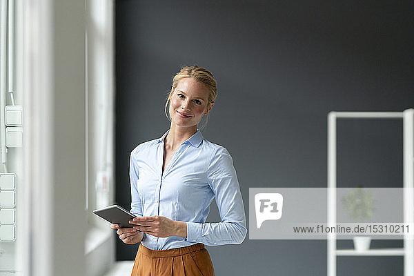 Porträt einer lächelnden jungen Geschäftsfrau mit Tablett im Büro
