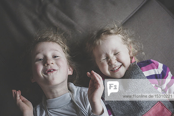 Portrait of two little sisters lying side by side on couch having fun  top view