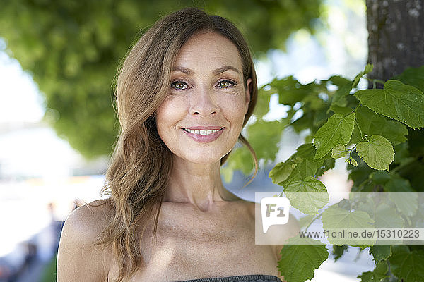 Portrait of mature woman  tree in the background