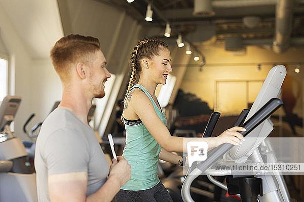 Junge Frau trainiert auf Steppmaschine im Fitness-Studio mit Personal Trainer