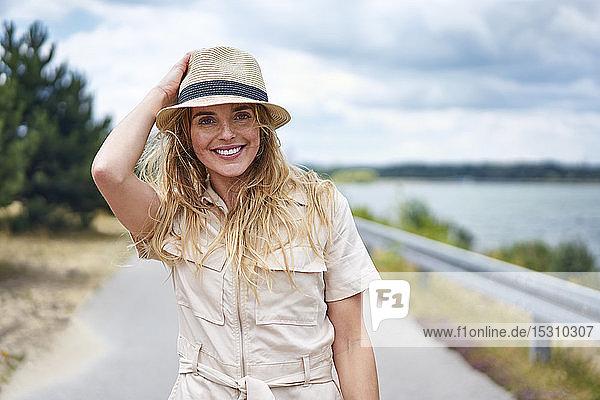 Porträt einer lächelnden Frau auf einer Landstraße am Seeufer