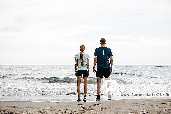 Junges Paar steht Seite an Seite am Strand