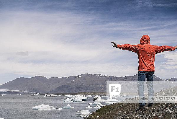 Ein erwachsener Mann betrachtet den Vatnajokull-Gletscher  Island  mit ausgestreckten Armen