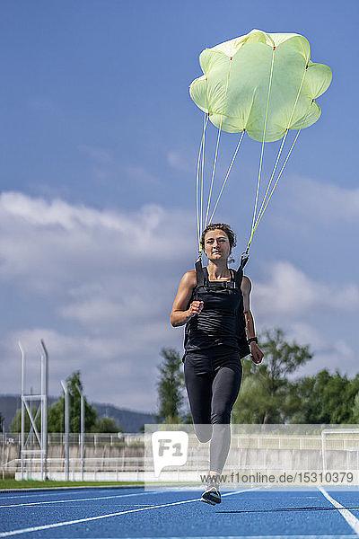Läuferin mit Fallschirm auf Tartanbahn