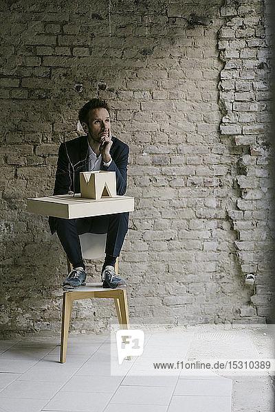 Geschäftsmann auf Stuhl sitzend mit Architekturmodell