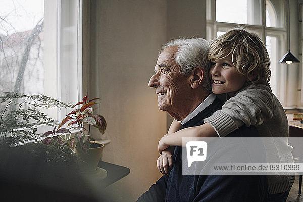 Glücklicher Enkel umarmt Großvater zu Hause