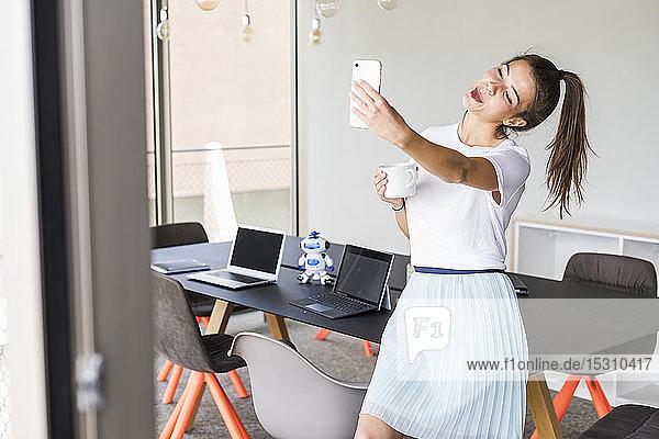 Junge Geschäftsfrau im Amt nimmt sich ein Selfie