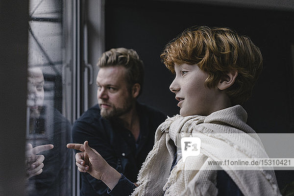 Boy and his father looking out of the window