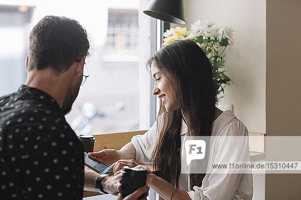 Junges Paar mit Einwegbecher und Smartphone in einem Cafe